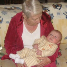 A great grandma wearing a red track suit and holding a baby in an orange and white jumper
