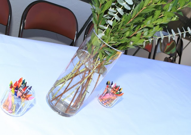 boxwood branches in a large glass vase, and crayons in small jars on a white tablecloth