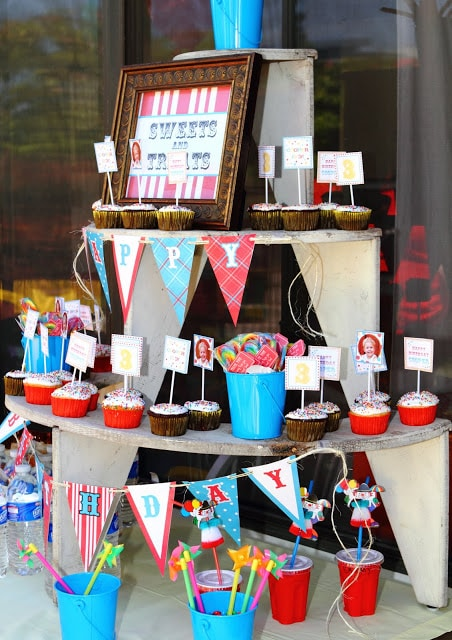 A large wooden stand holding carnival themed cupcakes, lollipops and toys
