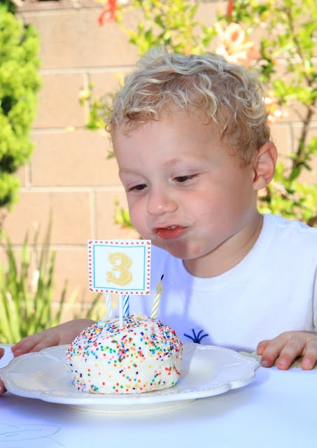 a little boy blowing out the birthday candle on his mini cake with sprinkles