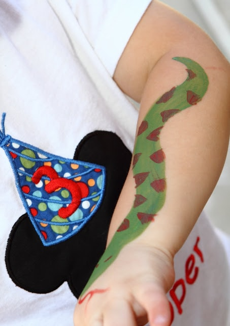 a child's arm with a watercolor snake