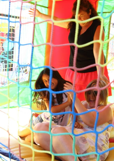 a child and two female adults playing in a bounce house