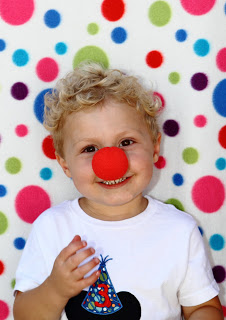 a toddler with a red clown nose standing in front of a colorful polka dot backdrop