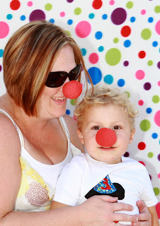 a toddler an mom with a red clown nose standing in front of a colorful polka dot backdrop