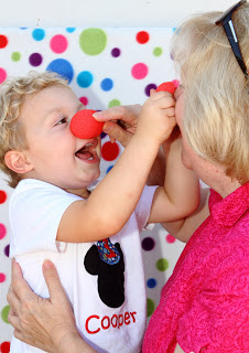 a toddler and grandma with a red clown nose standing in front of a colorful polka dot backdrop