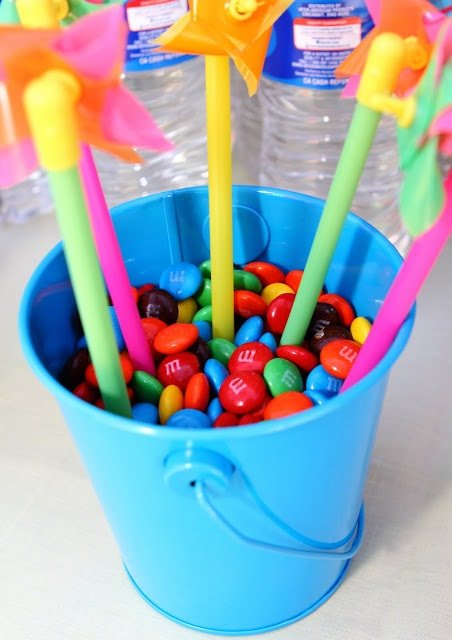A blue bucket filled with m&ms and tiny pinwheels