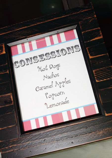 a brown wood framed sign listing concessions of hot dogs, nachos, caramel apples, popcorn and lemonade