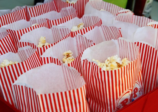 red and white striped popcorn bags filled with popcorn
