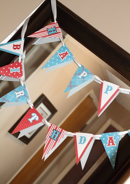 a red, white and blue happy birthday banner strrung up on a mirror