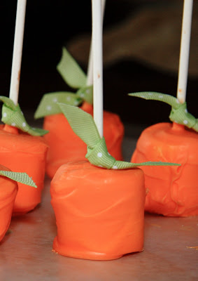 orange coated marshmallows on foil with a green ribbon and a white lollipop stick