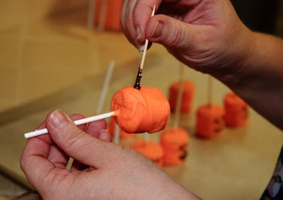 A hand holding a orange marshmallow on a lollipop stick and using a toothpick dipped in regular chocolate to draw a face
