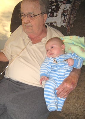 A grandpa sitting in a recliner holding his infant grandson