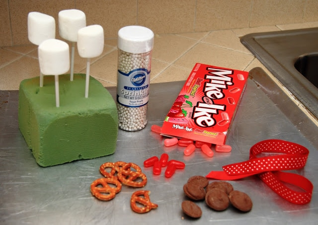 The supplies used to make reideer marshmallow pops - marshmallows on white lollipop sticks, red candies, pretzels and melting chocolate and red ribbon