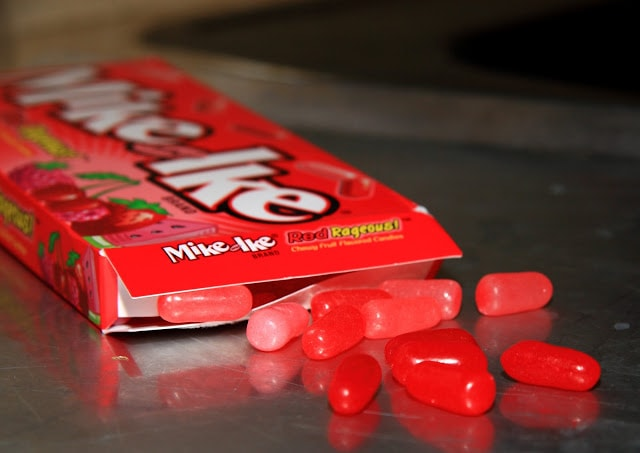 red mik and ikes candy spilling out of a box on a metal baking sheet
