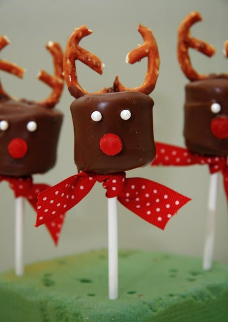 Chocolate covered Marshmallow pops with white sprinkles for eyes, a red candy nose and pretzel antlers