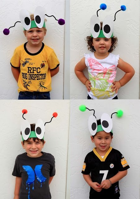 A group of children posing for the camera with bug hats