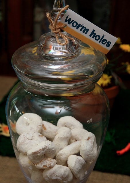 """Glass jar with treats and label that says \""""worm holes\"""""""