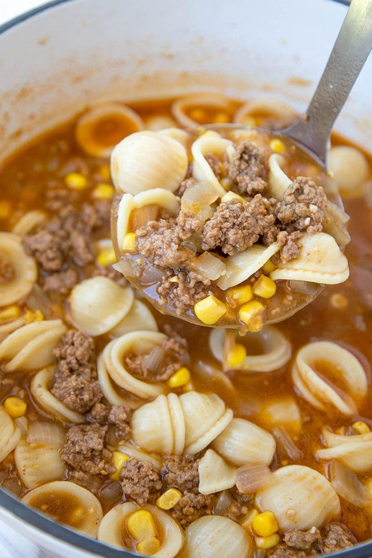 hamburger soup on a ladle with pasta and corn