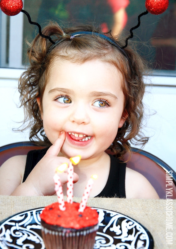 A young girl and a birthday cupcake with candles