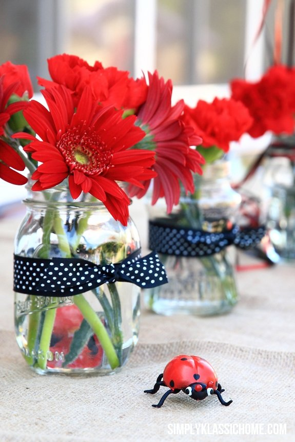 Clear vases of red flowers on a table