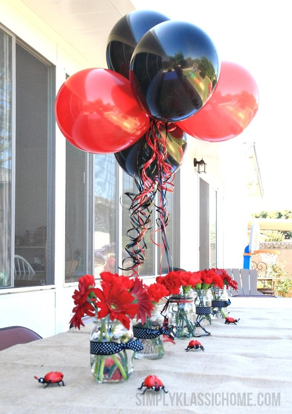 Vases of flowers and balloons on a table