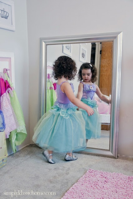 Little girl in princess dress in front of a mirror