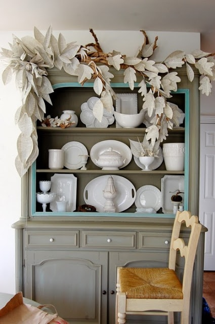 Book Page Garland in the shape of leaves on grey hutch filled with white dishes