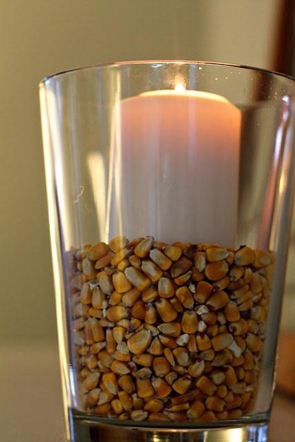 Corn kernels filling vase with candle inside
