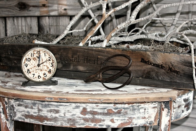 A clock, branches, and moss sitting on top of a wooden table