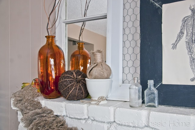 White mantel with fall decor including pumpkins, burlap, and amber colored vases