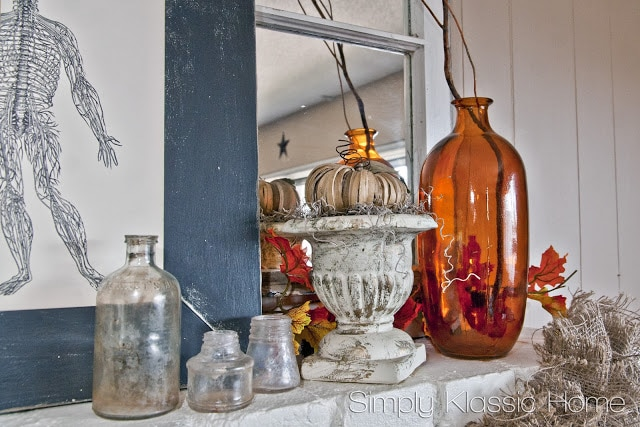 White mantel with fall decor including pumpkins and amber colored vases