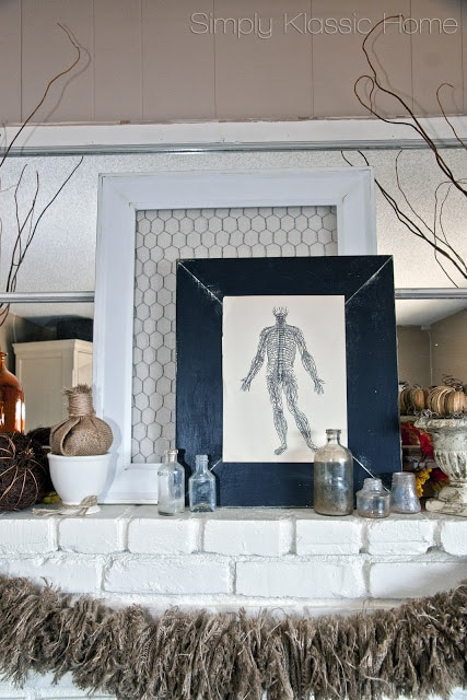 White mantel with fall decor including pumpkins, burlap, vintage anatomy print, and amber colored vases