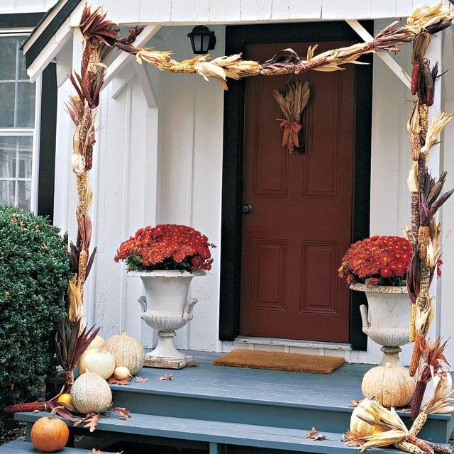 Decorated front door with corn cobs and pumpkins