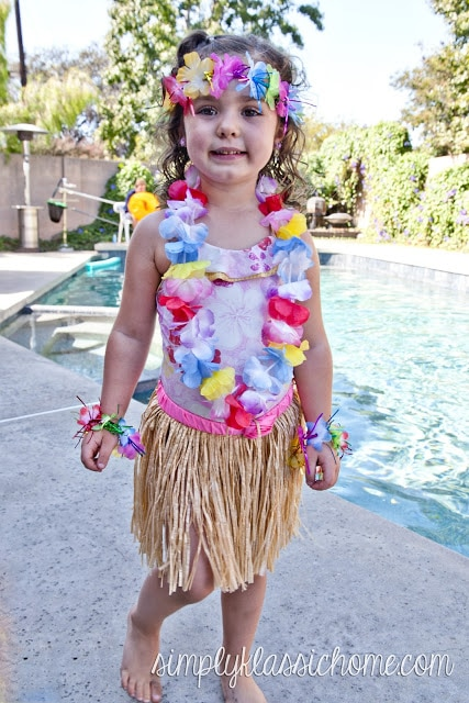 A little girl posing for a picture in front of pool