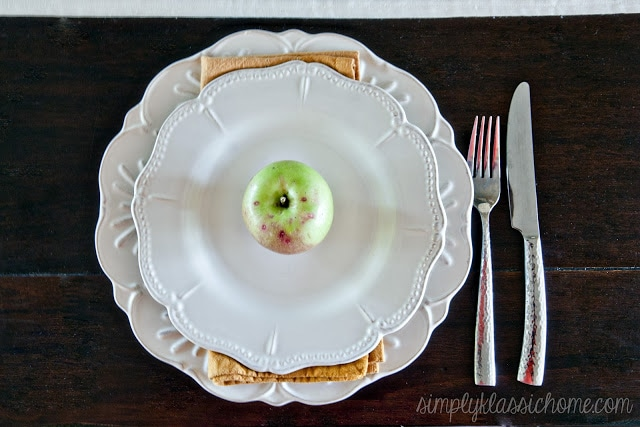 White tables with a green apple on top