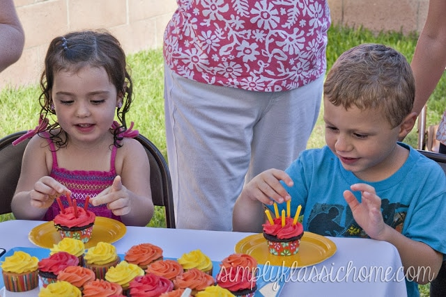A little boy sitting at a picnic table with cupcakes