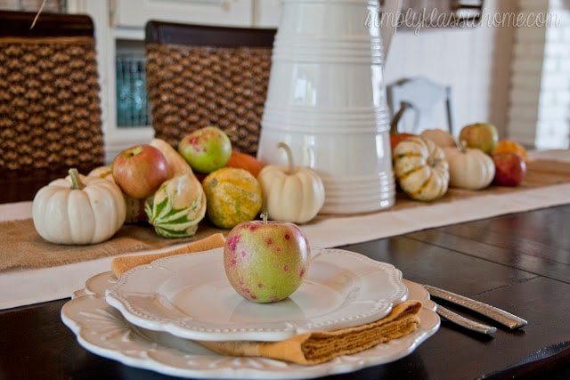 A close up fall decor and white plates on a dining table
