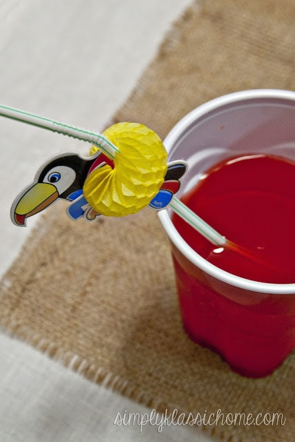 A cup of punch with a parrot straw