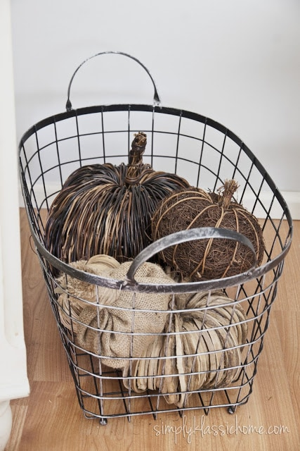 A basket filled with brown and beige pumpkins