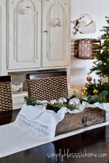 Dining room table with ornaments & pinecones centerpiece
