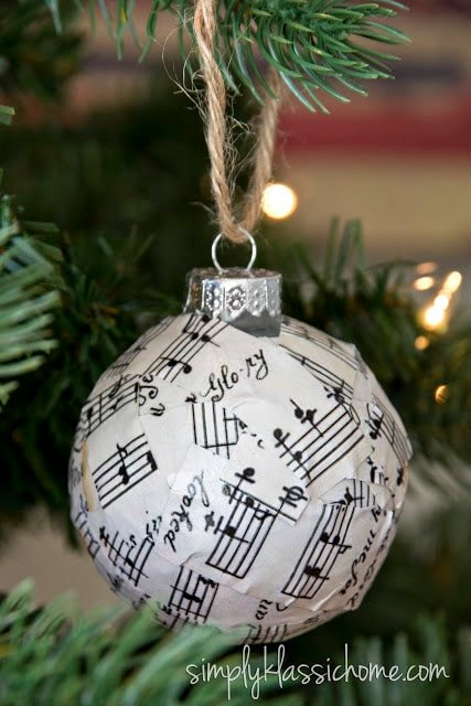 A close up of a glass ornament covered in sheet music