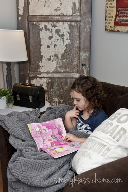Girl reading on brown chair