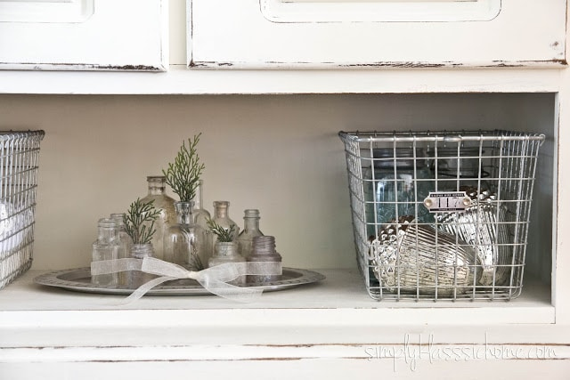 Decorative bottles on a white dining room hutch
