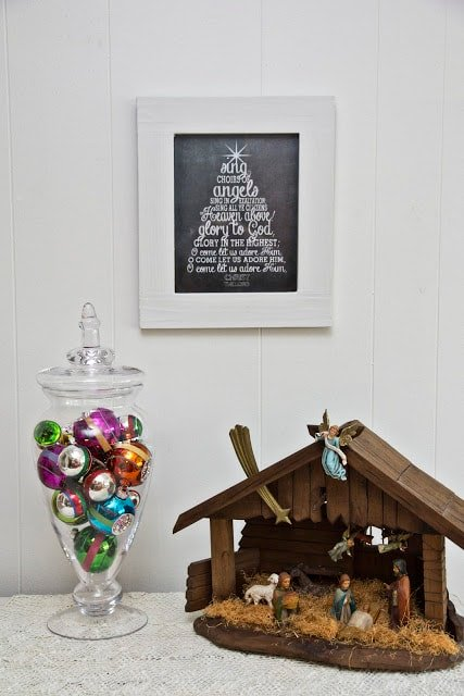 Christmas chalkboard print on a wall, vase with ornaments and a Nativity scene
