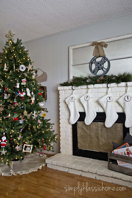 A living room with a Christmas tree and fireplace with stockings