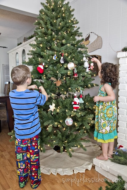 A little girl and little boy standing next to a christmas tree