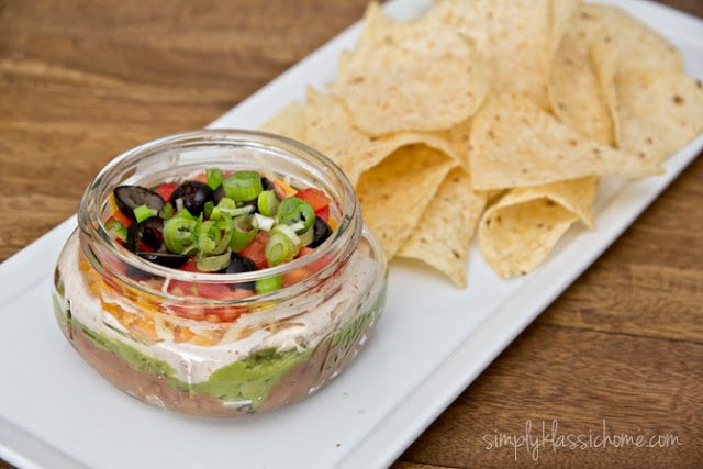 A bowl of Mexican dip with chips
