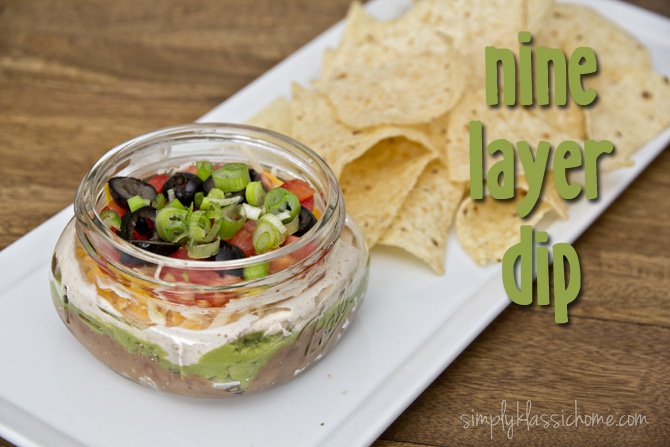 A jar of nine layer dip on a plate with chips