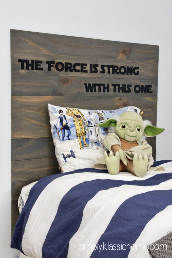 A stuffed Yoda and pillow on a bed