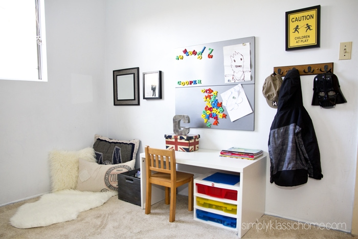 A bedroom with a desk and pillows on the floor